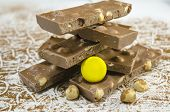 foto of sprinkling  - Dark chocolate on a cocoa sprinkled table decorated with hazelnuts - JPG