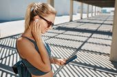 picture of sportswear  - Young fitness blonde woman in sportswear listening music with headphones after training outdoors at beautiful sunny day - JPG