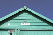 stock photo of beach hut  - Single beach hut and blue sky with plane flying over - JPG