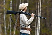 stock photo of hunter  - Woman hunter with gun in spring forest - JPG