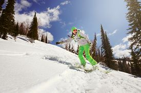 stock photo of snowboarding  - Snowboarder doing a toe side carve with deep blue sky in background - JPG