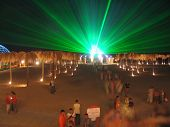 The Green Laser At Night Above A Beach, People Among Artificial Palm Trees