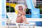 Young women in white bikini and white hat relaxing near waterpool