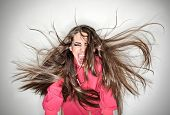 Screaming Furious Aggressive Brunette Woman With Flying Long Hairs, Ring Flash Studio Portrait On Wh