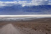 picture of sandstorms  - The bottom of a dry lake mountains with snow and a road in front in Death Valley - JPG