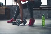 Closeup On Fitness Woman Taking Dumbbell From The Floor In Gym poster