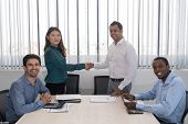 Happy Indian And Chinese Partners Shaking Hands At Business Meeting. Four Mix Raced Business Leaders poster
