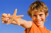 Happy Child With Starfish On Summer Vacation