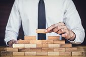 Risk To Make Business Growth Concept With Wooden Blocks, Hand Of Man Has Piling Up And Stacking A Wo poster
