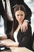 Businessman putting hand on assistant shoulder - sexual harrasment poster