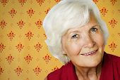 Senior woman portrait on a vintage wallpaper background