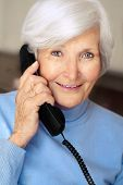 Senior woman portrait  with white hair and blue pullover holding phone receiver