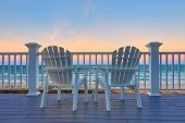 Empty Adirondack chair on a deck balcony overlooking the beach and the ocean at sunset poster