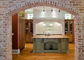 stock photo of armoire  - luxurious kitchen with butcher block counter seen through brick arch - JPG