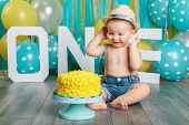 Portrait Of Cute Adorable Caucasian Baby Boy Wearing Jeans Pants And Hat Celebrating His First Birth poster
