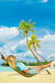 Woman relaxing at the beach on a hammock on Sentosa beach poster