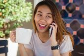 Happy Smile Asian Business Women Using Talking Cell Phone Sitting In Cafe And Holding A Cup Of Coffe poster
