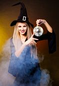 stock photo of witch ball  - sexy young blond witch with a disco ball against black and yellow studio background - JPG