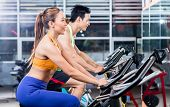 Sportive Asian couple doing indoor cycling side by side in a gym as endurance training poster