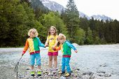 Children Hiking In The Alps Mountains Crossing River. Kids Play In Water At Mountain In Austria. Spr poster