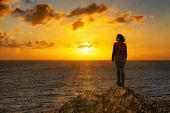 Adventurous Girl On A Rocky Ocean Coast Enjoying The Beautiful View Of The Colorful Sunset. Image Co poster