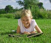 pic of girl reading book  - Smiling beautiful girl reading book on green grass  - JPG