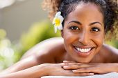 Closeup face of young african american woman in a wellness center ready for massage therapy. Portrai poster