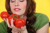 Woman smelling vine tomatoes