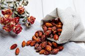 A Linen Bag With Dried Rose Hips And A Dried Branch Of Small Roses On A Light Wooden Table. The Conc poster