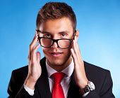 Funny portrait of a young business man with a nerd glasses trying to put them on