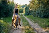 Young Girl Riding On A Pony Horse Along A Country Road poster