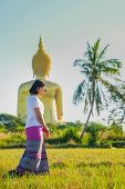 An Asian Women Walking And Walking Meditation The Temple In The Lawn Behind A Golden Buddha Image. poster