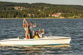Young friends waving from speed boat in the sunshine