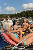 Women in bikini applying sunscreen lotion lying on deckchair