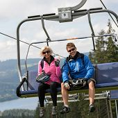 Young smiling couple sitting on chairlift