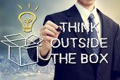 image of person writing  - Businessman drawing thinking outside the box theme - JPG