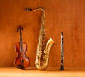 stock photo of violin  - Classic music Sax tenor saxophone violin and clarinet in vintage wood background - JPG