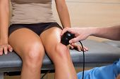 Ultrasonic therapy machine treatment doctor and woman patient on her knee