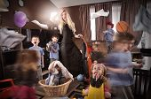 stock photo of babysitting  - A housewife is wearing a glamorous beautiful dress and cleaning the house while wild children are running around making a mess - JPG