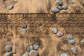 car tire footprint in a sand and rolling stones beach texture
