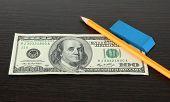 Making fake dollar on wooden background