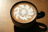 Latte Art, Designs drawn with steamed milk in hot fresh rich coffee in a ceramic coffee cup.