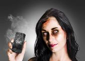 stock photo of gruesome  - Zombie business girl with bloodshot eyes holding smoking mobile phone with skull and crossbones in a depiction of dead technology - JPG