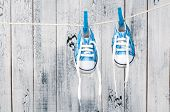 stock photo of clotheslines  - Baby shoes hanging on the clothesline - JPG