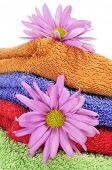 closeup of a pile of towels of different colors and some pink flowers on a white background