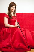 picture of riding-crop  - beautiful woman in a red ball gown sitting on a red couch and holding a riding crop - JPG