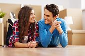 stock photo of legs apart  - Happy couple lying down in their new apartment - JPG