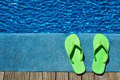 stock photo of swimming  - Green slippers by a swimming pool - JPG