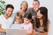 Smiling family watching something on laptop on the couch