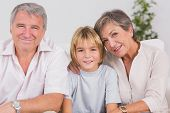 Portrait of a little boy and his grandparents smiling in sitting room